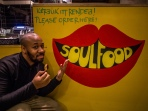 Erick by a Soul Food sign